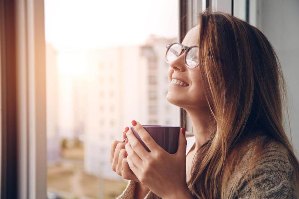 Mujer sonriendo con una taza de té en las manos para representar el JOMO