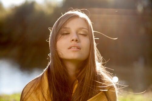 Mujer cerrando los ojos por su optimismo inteligente