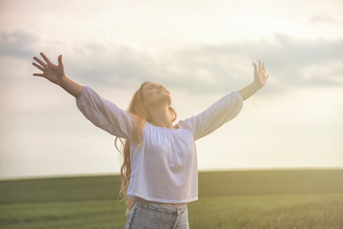 Mujer con los brazos abiertos por su optimismo inteligente