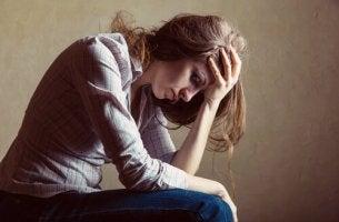Mujer con las manos en la frente pensando en sus ideas irracionales