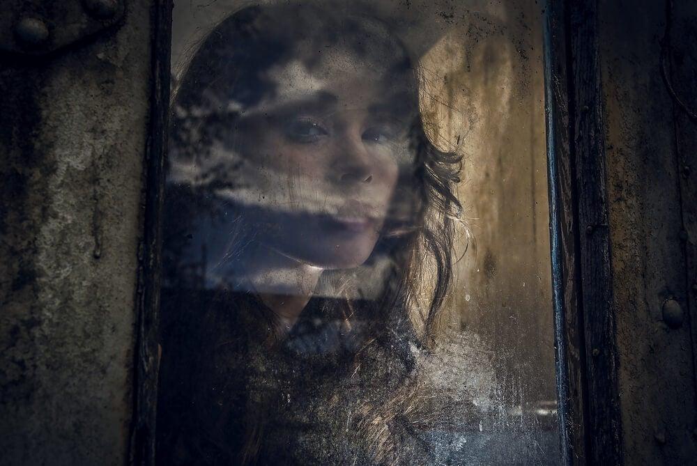 Mujer mirando a través de una ventana