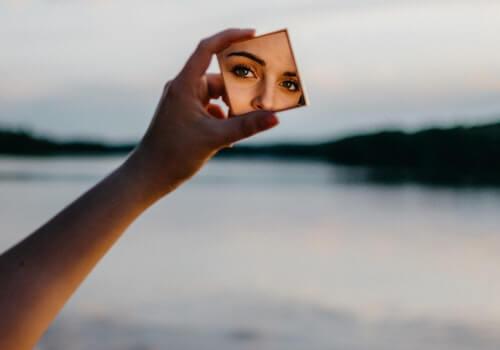 Mujer mirándose al espejo practicando el arte de ser sinceros