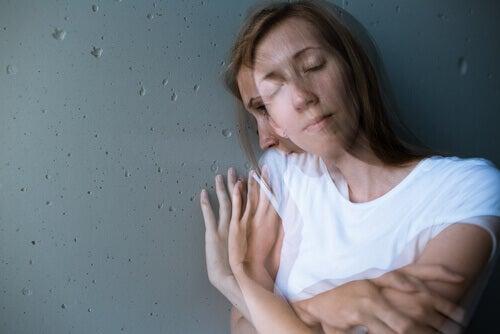 Mujer abrazándose con pensamientos negativos