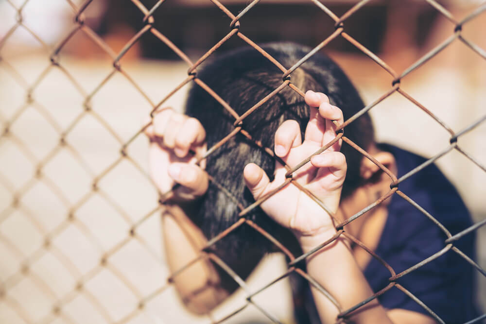 Mujer llorando agarrada a una alambrada