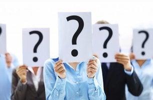 Personas con un cartel con una interrogación en sus caras