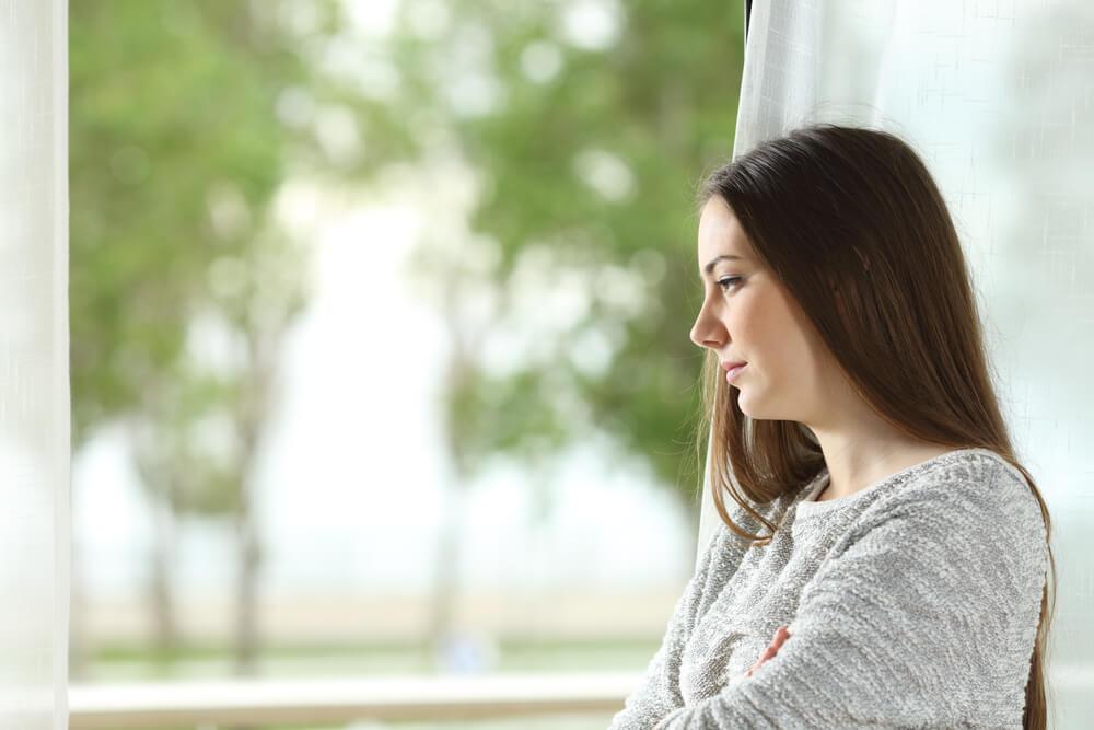 Mujer melancólica pensando en cómo eliminar la dependencia emocional de su vida
