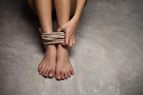 Pies de una mujer atados con una cuerda