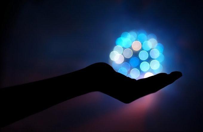 Mano sujetando una esfera de bolas azules