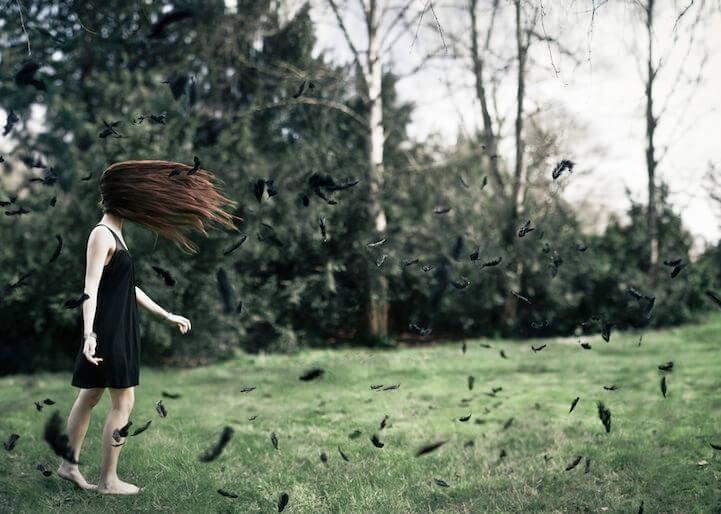 Mujer caminando entre plumas negras sin llegar a alcanzar la felicidad