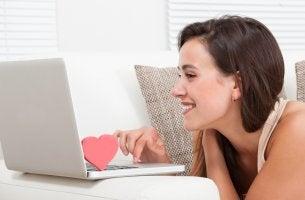 Mujer con un corazón en el ordenador hablando por internet