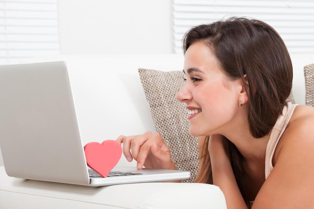 Mujer con un corazón en el ordenador simbolizando relaciones cibernéticas