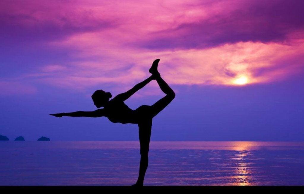 Mujer disfrutando de los beneficios del yoga en la playa