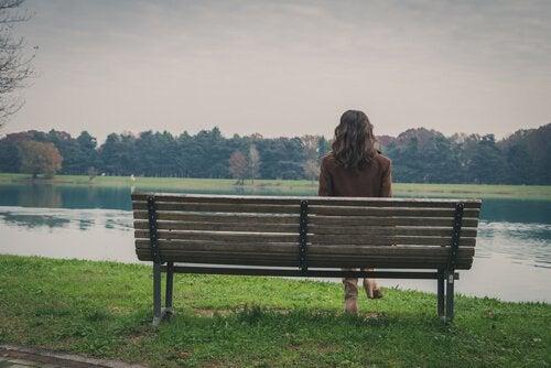 Mujer sola en un parque intentando cerrar puertas