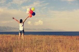 Mujer con globos pensando en la actitud positiva