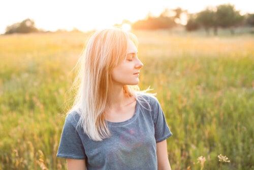 Mujer agradecida con los ojos cerrados representando que necesita mucho para ser feliz