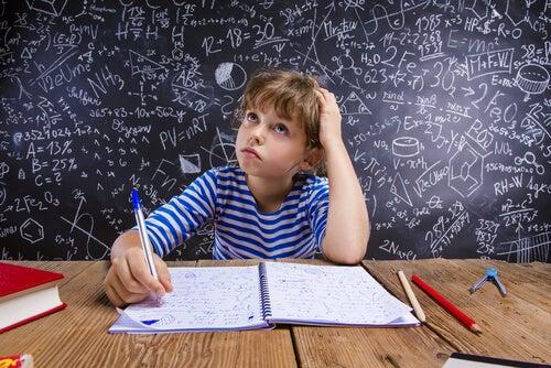 Niño pensando mientras hace los deberes