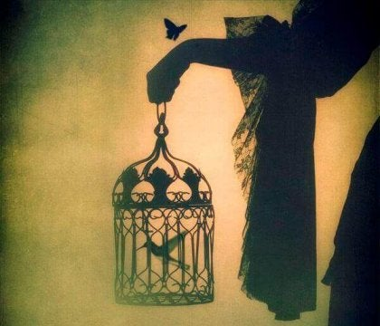 Siniestra imagen de una mano sosteniendo una jaula