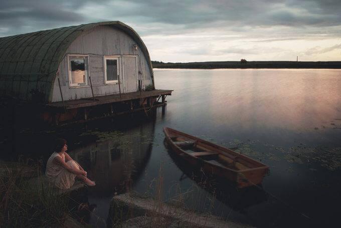 Mujer con miedo sentada al lado del río