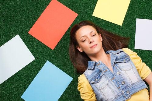 Mujer tumbada sonriendo por un pensamiento positivo