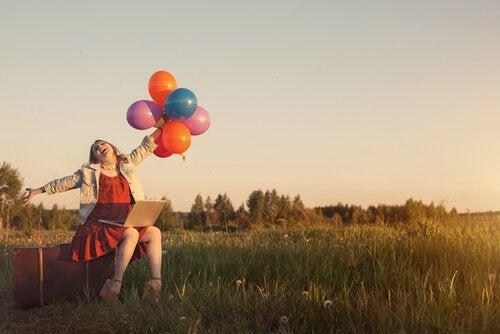 Mujer con pensamiento positivo sujetando globos de colores