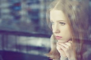mujer mirando por la ventana pensando en que se arrepiente