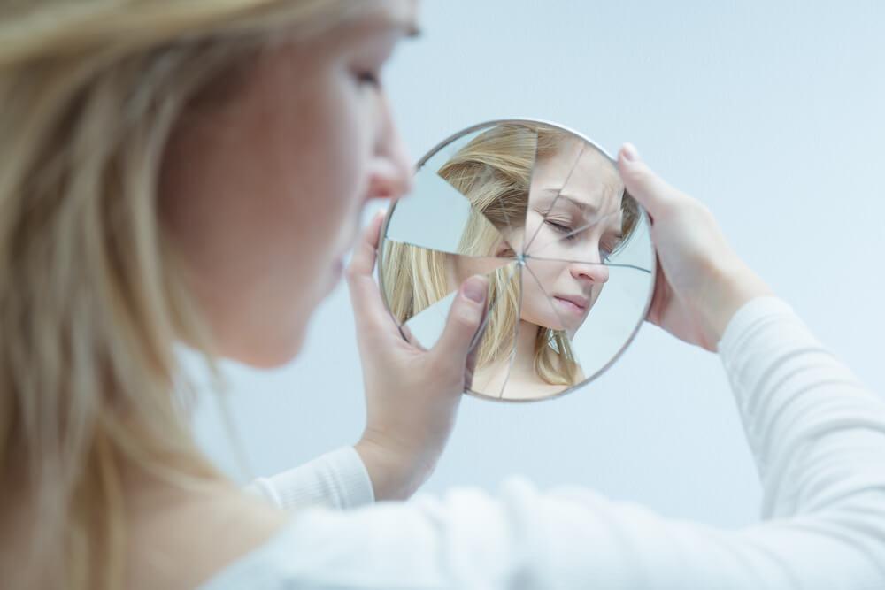Mujer mirándose a un espejo roto