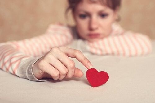 Mujer con filofobia tocando un corazón