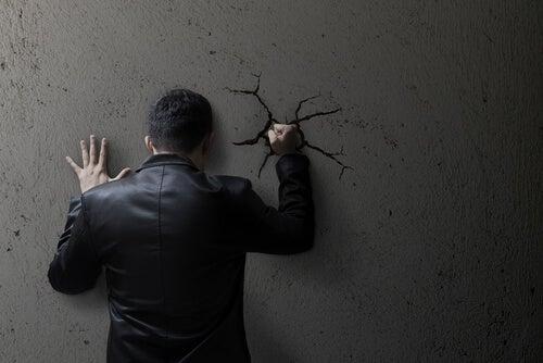Reprimir las emociones, hombre golpeando la pared