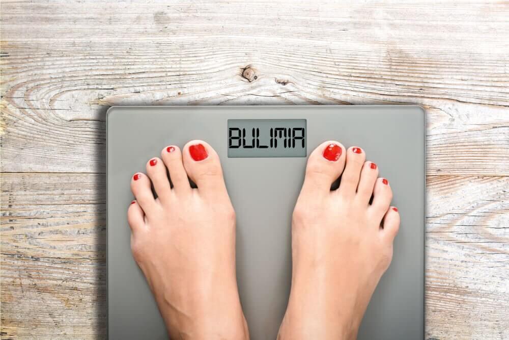 Chica en una báscula que pone bulimia