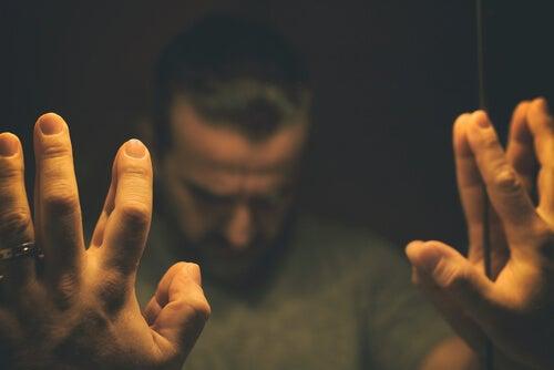Hombre ante une spejo con pensamientos distorsionados