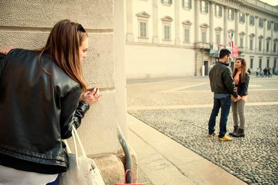 Mujer celosa espiando a alguien que cree es de su propiedad