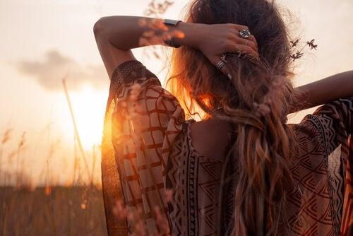 Mujer de espaldas disfrutando la serenidad del atardecer