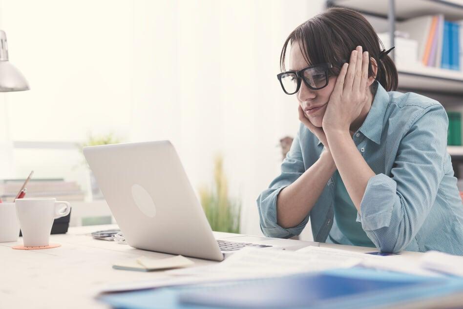 Mujer mirando al ordenador aburrida