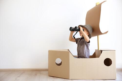 Niño jugando en barco de cartón
