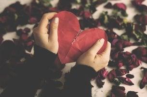Manos rompiendo un corazón para terminar una relación de pareja