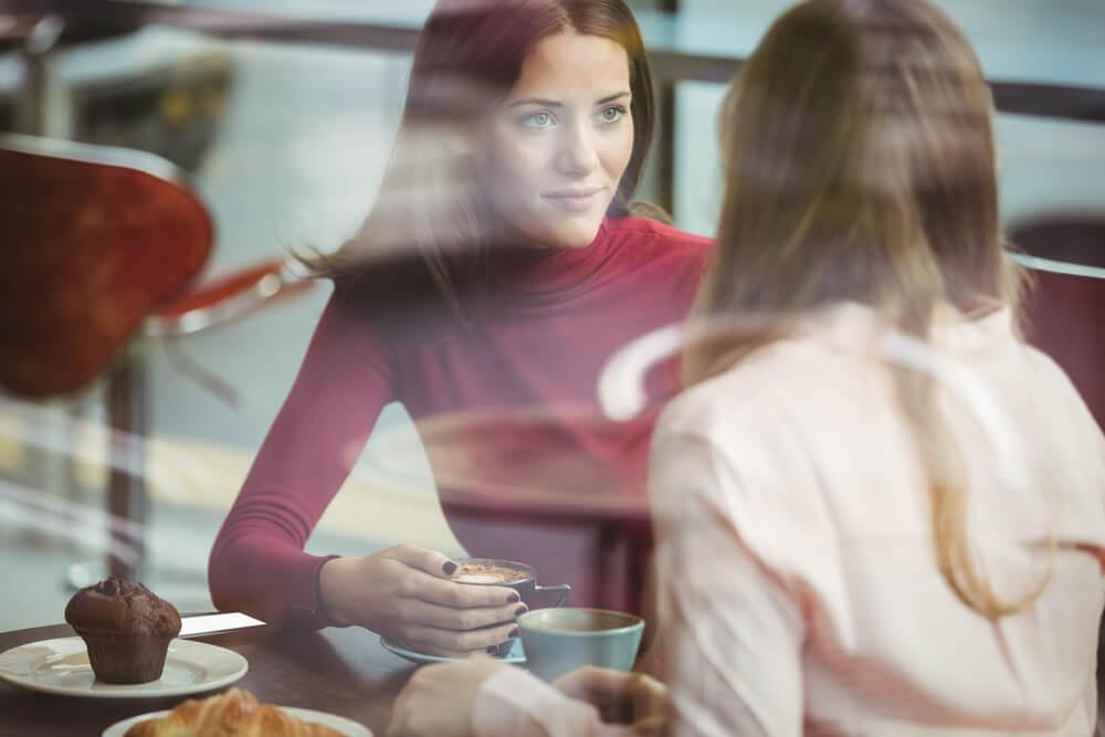 amigas hablando en cafetería simbolizando el arte de expresar el dolor emocional