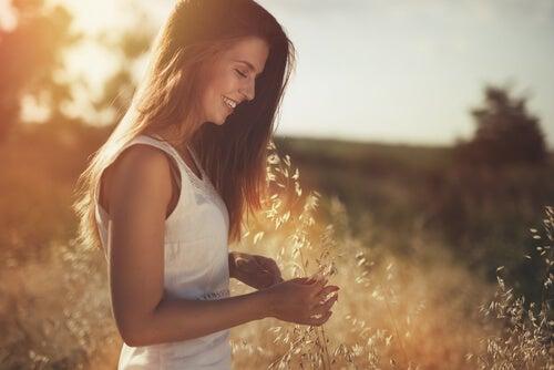 Mujer feliz en el campo pensando que pensando que agradezco todo lo que he superado