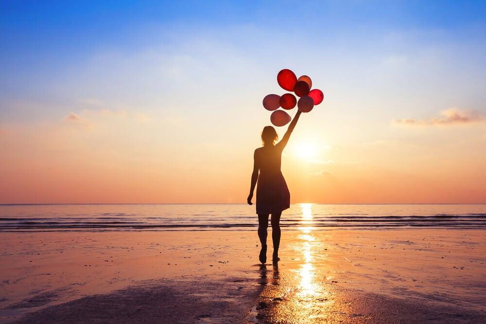 Mujer en una playa con globos