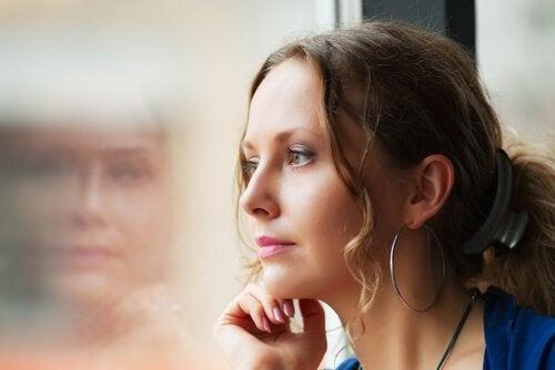 Mujer mirando por una ventana en soledad