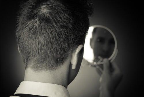 Hombre con miedo mirándose al espejo