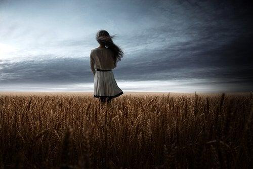 Mujer sola en el campo pensando en el destino