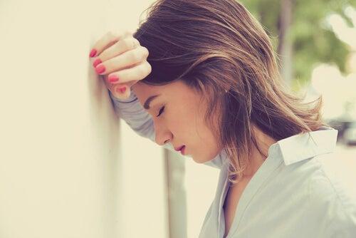 Mujer apoyada en la pared con dolor de cabeza