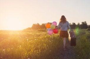 Mujer con maleta y globos que ha vencido al pesimismo