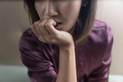 Mujer con miedo comiendo uñas
