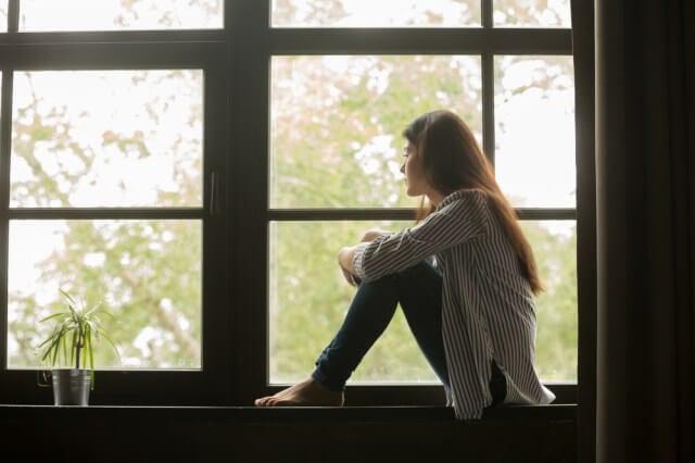 Mujer mirando por la ventana melancólica
