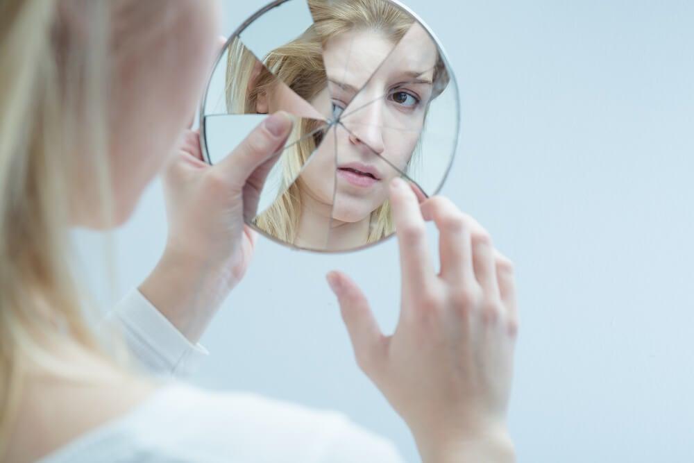 Mujer mirándose en espejo roto
