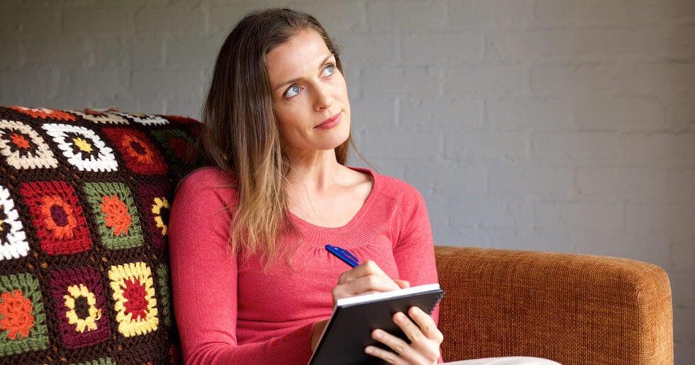 Mujer escribiendo su plan de la jornada simbolizando las cosas que puede hacer antes de las 9