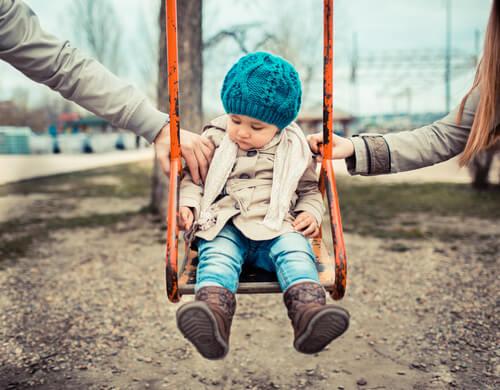 Niño en columpio en medio de sus padres