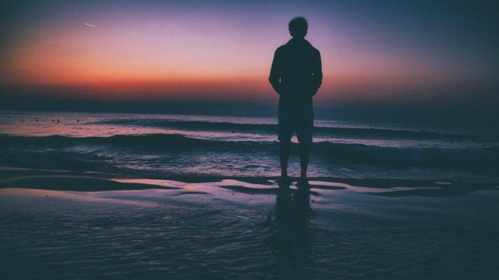 Hombre solo mirando al mar debido a la desesperanza en la depresión