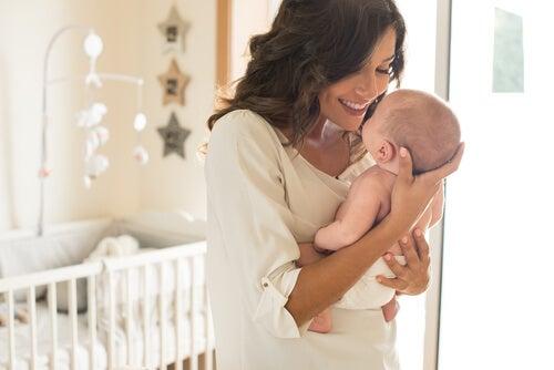 Mujer feliz levantando a su bebé con las manos